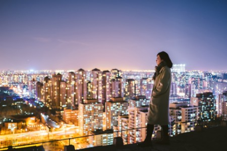 Woman overlooking city at night